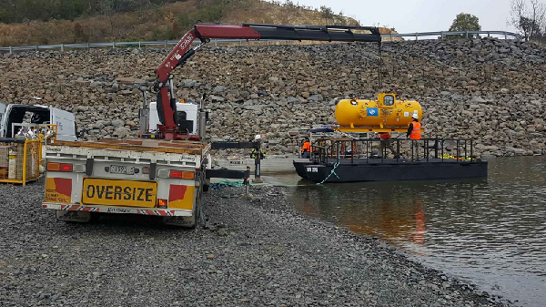 Lake Eildon hyperbaric chamber being loaded onto barge