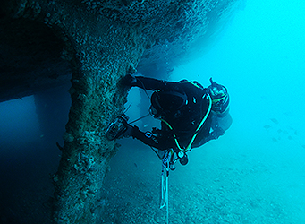 Commercial diver inspecting sunken vessel