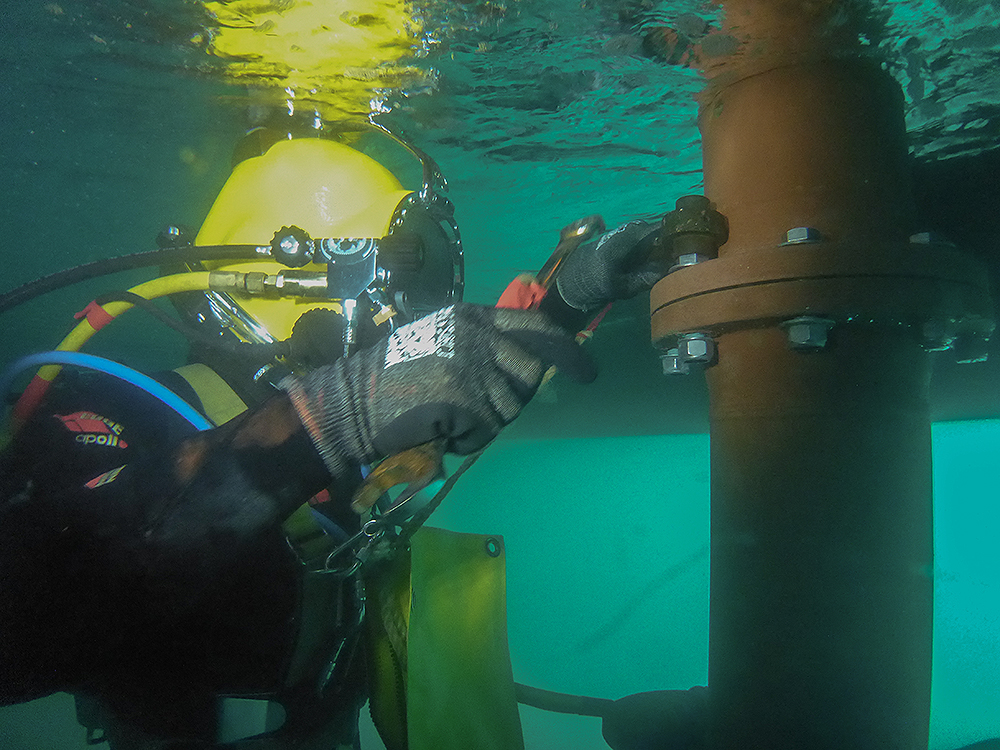Commercial diver using wrench under vessel
