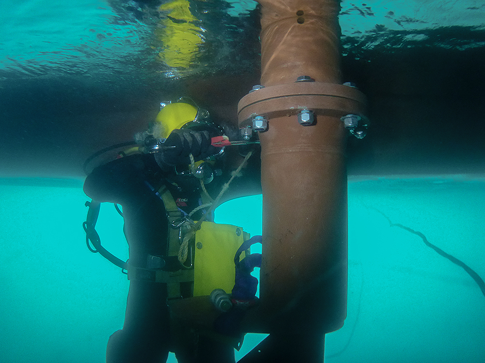 Commercial diver working under ship