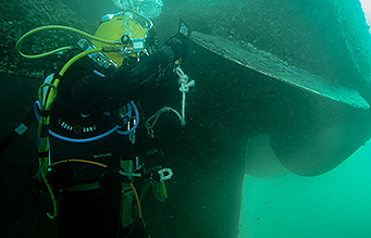 Diver polishing propeller